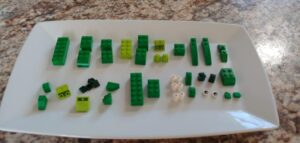 green lego pieces on a plate to make a dinosaur