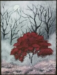 image of a red blossomed tree in the midst of dead trees
