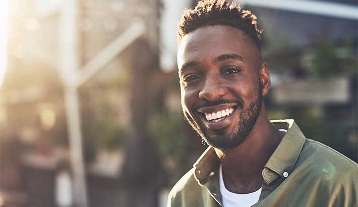 Young black man smiling at camera, sun shining in the blurred background