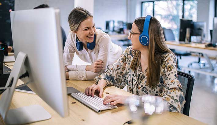 Two young white women laughing together, one is sitting in a chair typing on a computer, the other kneeling down next to her, both have blue headphones on