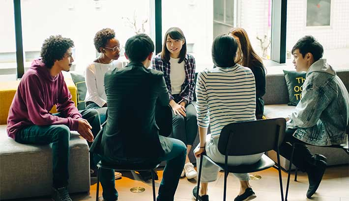 Group of diverse young adults sitting in chairs in a circle having a discussion.