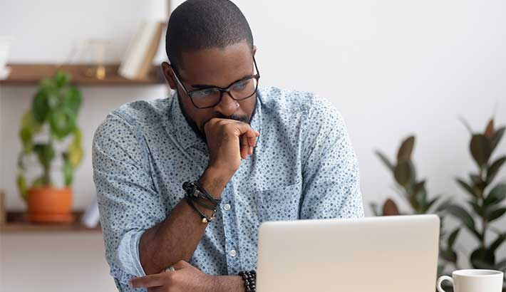 Black man wearing glasses looking at laptop screen with fisted hand covering mouth, coffee cup next to laptop