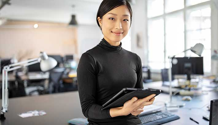 Asian woman holding a tablet and smiling at the camera, with office space blurred in background.
