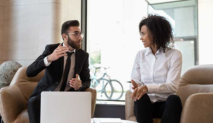 Man with beard and glasses sitting in chair on left, having a discussion with black woman on right, both sitting in work setting, man with laptop in front of him.