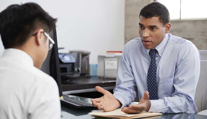 Black man sitting at desk dressed in a suit looking at younger asian man who has his back towards the camera sitting across from first man.