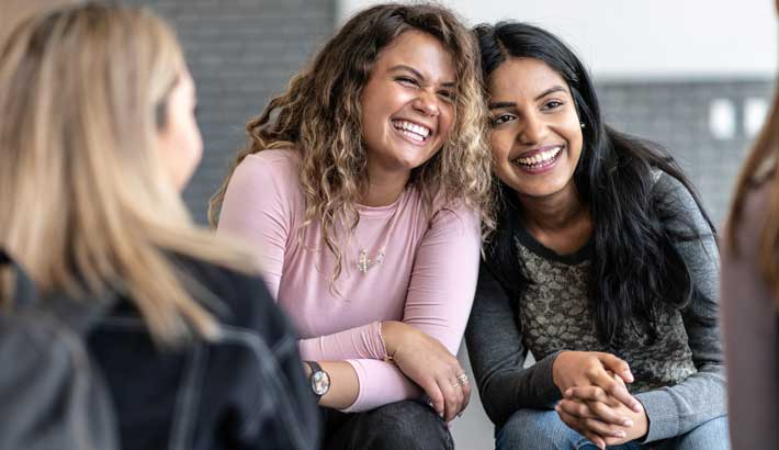 Group of three young adult women, two facing the camera and one with back facing camera, all laughing together
