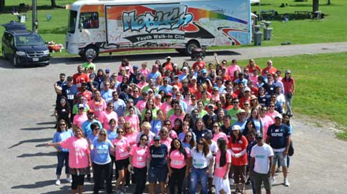 Overhead photo of large group of people in brightly coloured shirts, standing in front of a mobile youth walk-in clinic