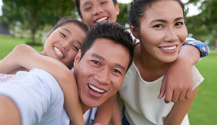 Asian family of 4: A male, female and two children, all hugging and smiling close to the camera.