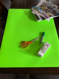 Green empty poster board with newspaper, scissors, marker and tape