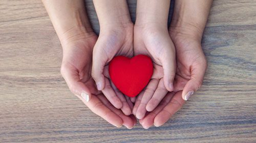 hands holding a heart being held by another pair of hands