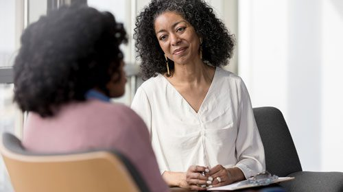 Black woman smiling with her hands crossed at young female patient