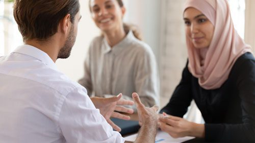 three diverse individuals having a discussion with the man explaining with his hands
