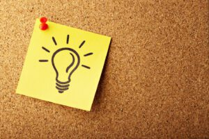 picture of a light bulb on a yellow sticky note thumbtacked to a bulletin board
