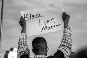 black man holding up black lives matter sign in the air
