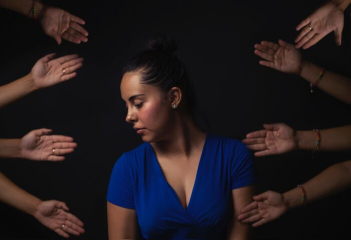 sad woman with hands stretched out towards her around her