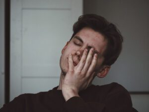 Young man stressed with hand pressed against face for hearing voices