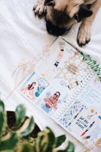 small dog on sheets next to a journal filled with colourful images and text
