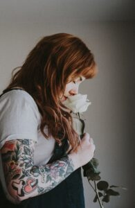 woman with her nose into a white rose smelling
