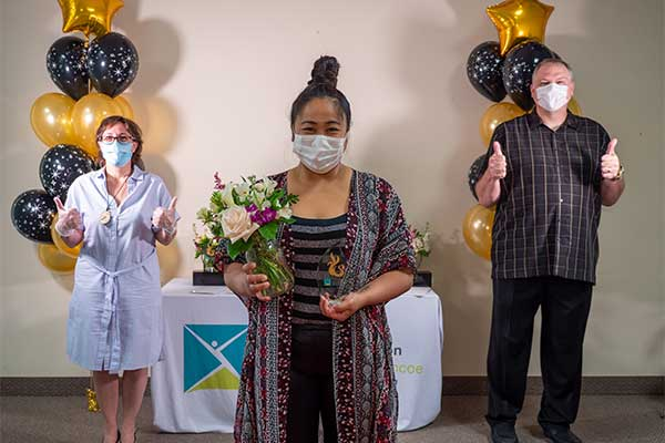 Jasmine wearing her mask and holding team award with flowers
