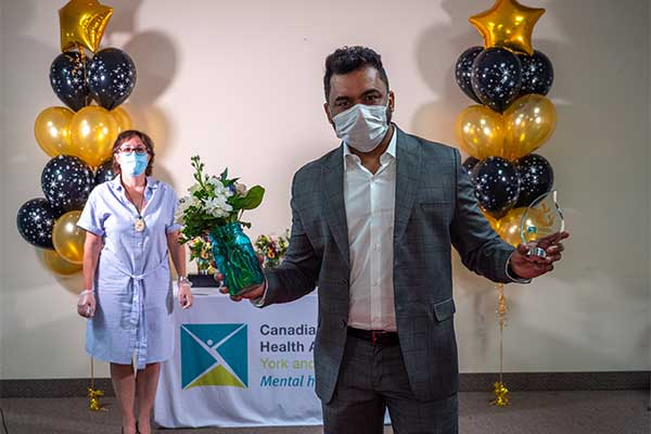 mohammed holding his Team Award with Canadian Mental Health Association