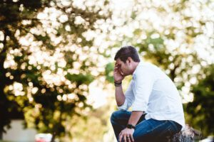 man holding his head in his hand outside with distressed face going through a tough time
