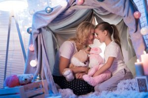 mother and daughter smiling in a house fort holding stuffed animals
