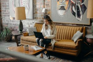 woman sitting on a couch in a living room with laptop in her lap