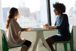 mental health counsellor speaking to a teenage girl at a table