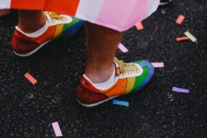 closeup of rainbow shoes with colourful confetti to represent pride