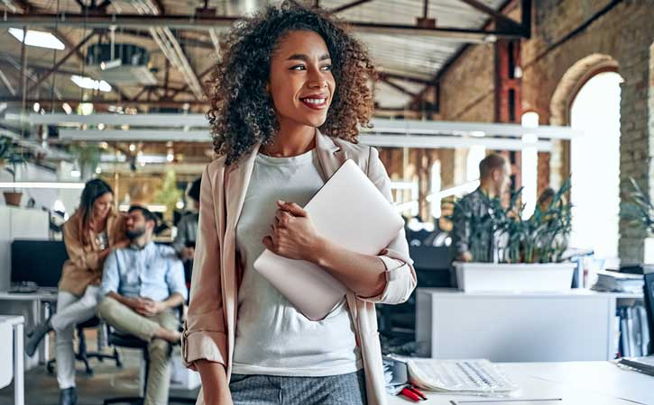 Young black woman standing centred in front of the camera, holding her laptop and smiling off the the right-hand side.