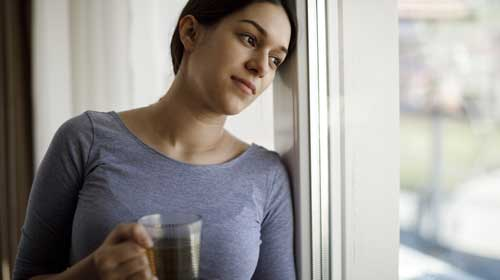 female holding a mug with her head against the window looking outside