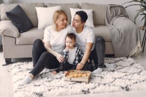 Family eating pizza in front of couch
