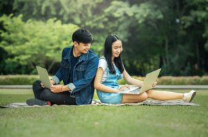 two young students sitting on the field with laptops back to back