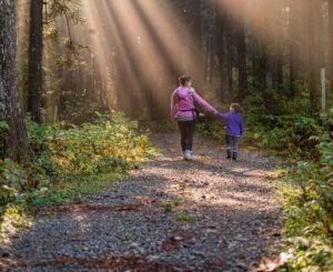 Mother and child going on a hike in the woods holding hands
