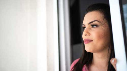 woman wearing a pink shirt looking outside