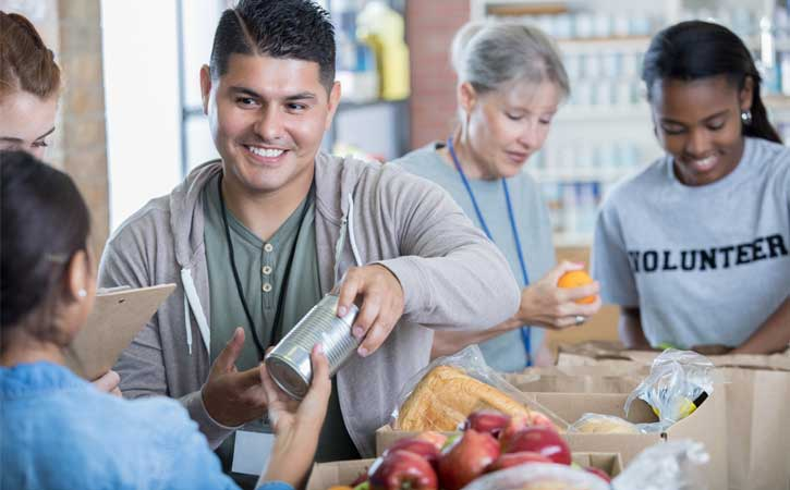 Group of three volunteers organizing food items in boxes, male volunteer handing a can to a person outside of the screen.