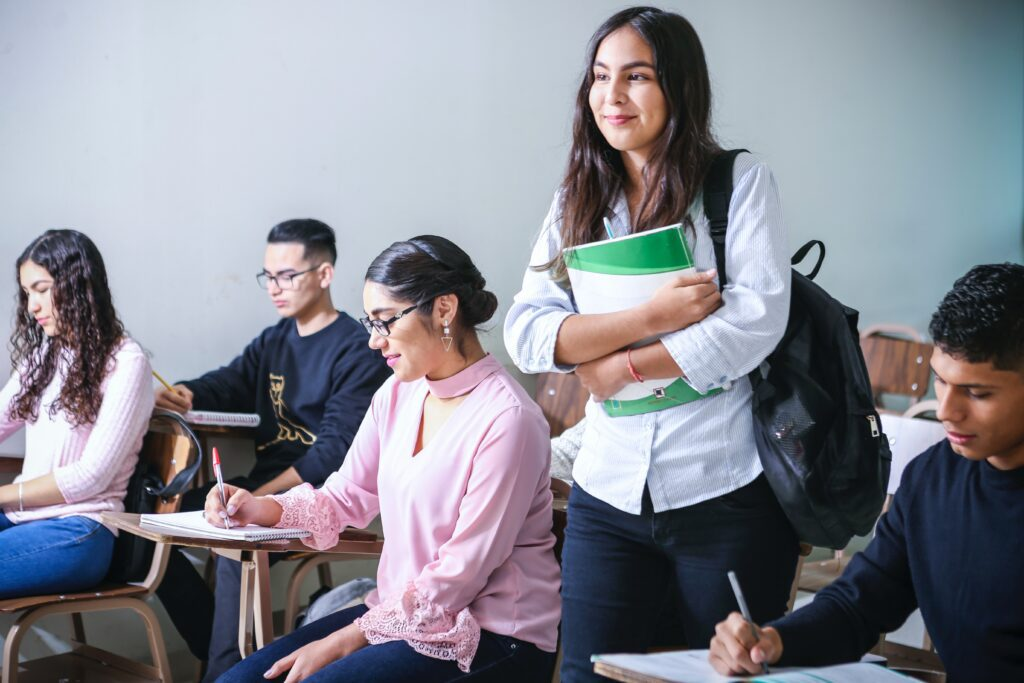 Female student holding her notebook and standing in the middle of her class of other students