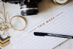 Closeup of a weekly agenda planner and a sharpie on top