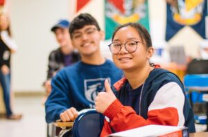 female student with her thumb up smiling sitting in class with students in the background