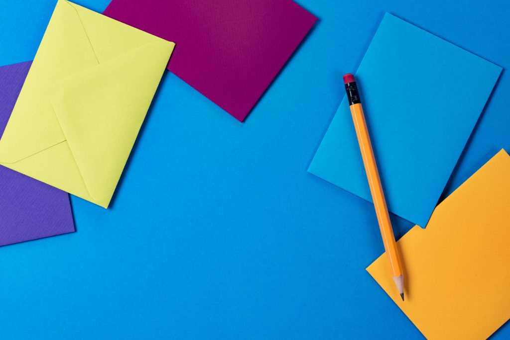 colourful envelopes on a table with pencil