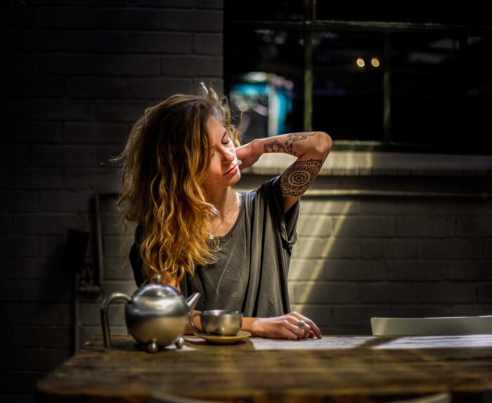 young woman with tattoos stretching her arm at a kitchen table