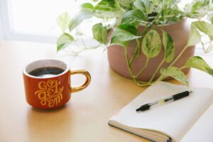 mug with coffee, open journal and plant on a table