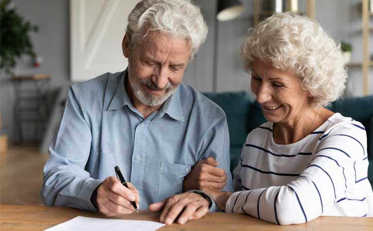 Elderly couple, arms linked, smiling while signing a document