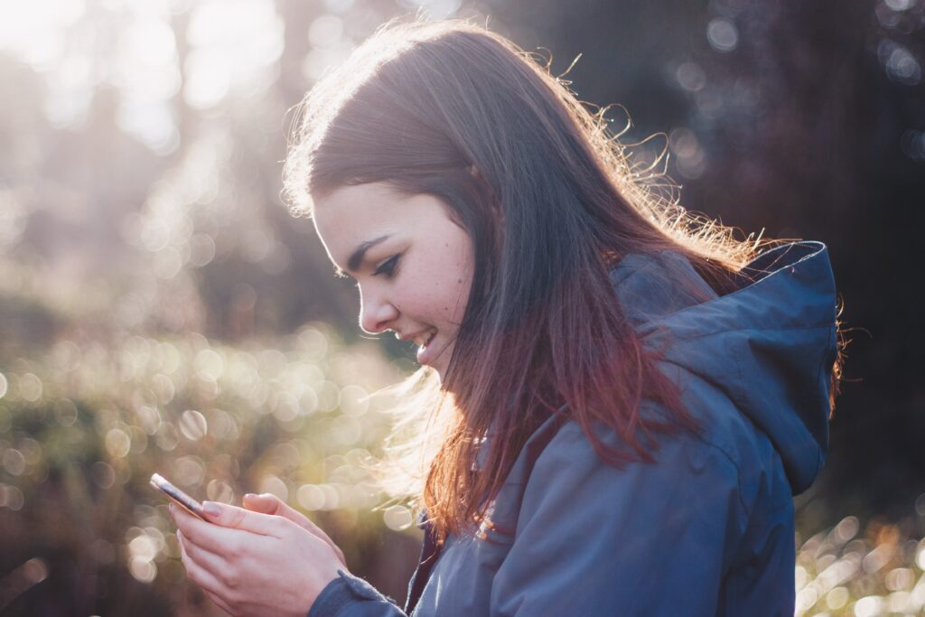 young female girl smiling at her smartphone screen