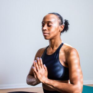 young black woman with her hands pressed together practicing mindfulness