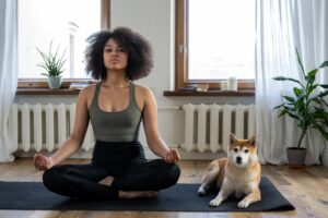 young black woman and dog sitting on a yoga mat and using meditation for mental health