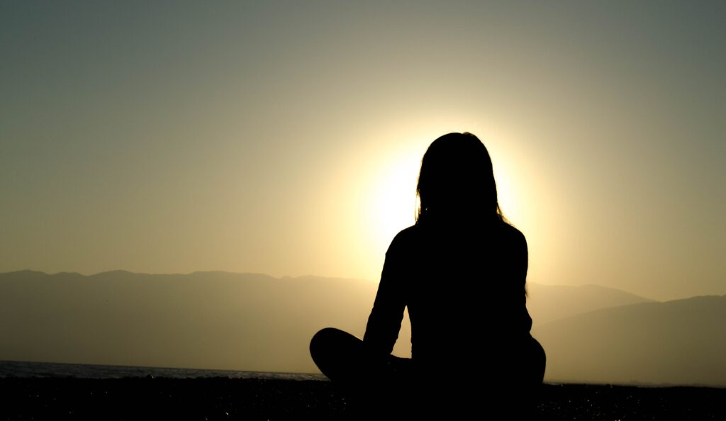 young woman sitting silhouette in the sunrise doing meditation