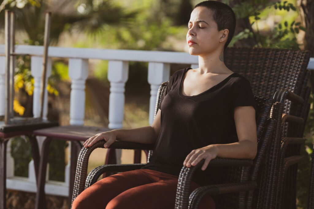 woman sitting on a patio chair with eyes closed meditating