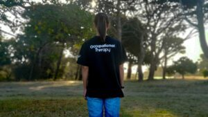 """woman wearing a black """"occupational therapy"""" shirt written across the back"""