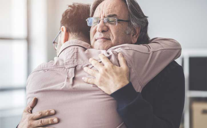 Grey-haired man with glasses hugging another man, one facing the camera and the other facing away